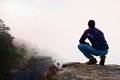 Hiker in squatting position on a rocky peak and enjoy the misty scenery rock Stock Photography