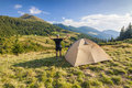 Hiker standing near tourist tent in mountains Royalty Free Stock Photo