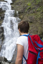 Hiker standing near waterfall young man by scenic Royalty Free Stock Photos