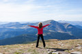 Hiker standing on a peak over the mountain with raised hands Royalty Free Stock Photos