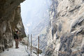 Hiker on steep mountain path a hike looks at the rocky cliffs in tiger leaping gorge in yunnan province near lijiang in china Royalty Free Stock Photography