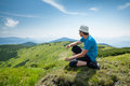 Hiker takes rest during hiking in mountains Stock Photo
