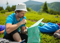 Hiker takes rest during hiking in mountains Stock Photos