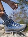 Hiker tying boot laces, high in the mountains Royalty Free Stock Photo