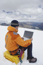 Hiker using laptop on snowy mountain landscape rear view of a male Stock Photo