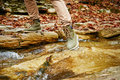 Hiker woman crossing a stream, view of legs Royalty Free Stock Photo
