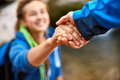 Hiker woman getting help helping hand on hike smiling happy overcoming obstacle tourist backpackers walking in autumn forest young Stock Image