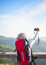 Hiker woman take a photo on the mountain, background blue sky