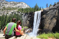 Hikers couple resting in yosemite park waterfall national enjoying view of beautiful vernal fall young hiking relaxing after hike Royalty Free Stock Photos