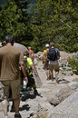 Hikers descend a mountain path group of five working their way through the rocks and boulders Royalty Free Stock Photos