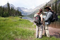 Hikers discuss the right direction stopped on a lake and Royalty Free Stock Photography