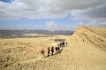 Hikers in negev desert israel national trail on the edge of big crater Stock Photo