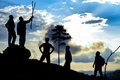 Hikers reaching summit at sunset Royalty Free Stock Photo