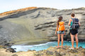 Hikers travel couple tourists hiking on hawaii tourist backpackers walking green sand beach papakolea big island usa Royalty Free Stock Images