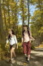 Hikers walking on path through forest full length of two female Royalty Free Stock Photography