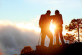Hiking adventure healthy outdoors people standing talking couple enjoying sunset view above the clouds on trek video of young Stock Photo