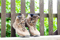 Hiking boots resting are at the garden fence Royalty Free Stock Images
