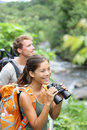 Hiking couple of hikers in outdoor activity wearing backpacks woman hiker looking with binoculars smiling happy healthy lifestyle Royalty Free Stock Photos