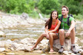 Hiking couple hikers resting in zion park national young women and men hiker sitting by river water creek enjoying view smiling Royalty Free Stock Images