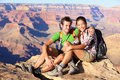 Hiking couple portrait hikers in grand canyon enjoying view of nature landscape looking at camera smiling happy young Stock Photos