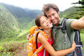 Hiking couple young couple in love on hawaii active taking self portrait picture hike man and women hiker trekking waihee ridge Royalty Free Stock Images