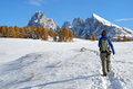 Hiking in the dolomites in autumn female tourist on alpe di siusi seiser alm towards sasso lungo langkofel mountain peaks through Royalty Free Stock Images