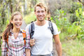 Hiking hikers walking happy in forest hiker couple laughing and smiling interracial couple caucasian men and asian women on big Royalty Free Stock Photography
