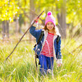 Hiking kid girl with backpack in autum poplar forest trees and walking stick Stock Photos