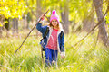 Hiking kid girl with backpack in autum poplar forest trees and walking stick Royalty Free Stock Images