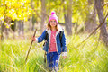Hiking kid girl with backpack in autum poplar forest trees and walking stick Stock Photo
