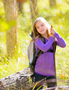 Hiking kid girl with backpack in autum poplar forest trees and walking stick Royalty Free Stock Photo