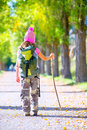Hiking kid girl with walking stick and backpack rear view at autumn track camouflage pants Stock Photography