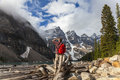 Hiking man looking at moraine lake rocky mountains with rucsac backpack standing on tree log by snow covered mountain peaks banff Royalty Free Stock Photography