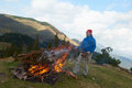 Hiking man try to light fire adventure collecting woods for Royalty Free Stock Photography