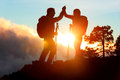 Hiking people reaching summit top high five giving at mountain at sunset happy hiker couple silhouette success achievement and Stock Photography
