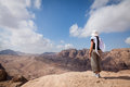 Hiking in petra woman is admiring a view of jordanian desert while Stock Photography