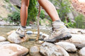 Hiking shoes on hiker outdoors walking crossing river creek woman hike trekking in nature close up of female boots in Stock Photography