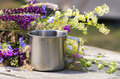 Hiking steel mug stands on a gray wooden table near the flowers Stock Images