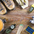 Hiking or travel equipment with boots, compass, binoculars, matches on wooden background. Active lifestyle concept Royalty Free Stock Photo