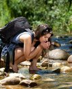 Hiking woman drinking water with hands from stream young bag Stock Photography