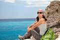 Hiking woman female tourist sitting on a rock against the sea Royalty Free Stock Photos