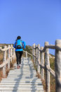 Hiking woman running at mountain stairs back of up Stock Photo