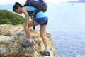 Hiking woman young climbing seaside rock Stock Photo