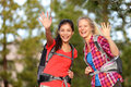 Hiking women waving hello smiling at camera happy with hands during hike trek outdoors in forest two beautiful girls living active Stock Image