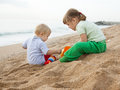 Hildren playing with sand at sea two beautiful girls play on the beach Royalty Free Stock Photos