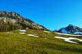 Patches of snow on green meadows with hillside chapel in mountainous region Royalty Free Stock Photo
