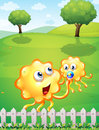 A hilltop with an orange monster playing with a baby monster illustration of Royalty Free Stock Photo