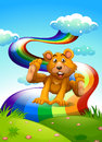 A hilltop with a playful bear near the rainbow illustration of Stock Photos