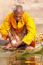 Hindu monk cleaning prayer utensil Royalty Free Stock Photography
