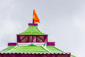 Hindu temple spire top above the shrine of a with the holy flag on top of a dome roof Stock Images